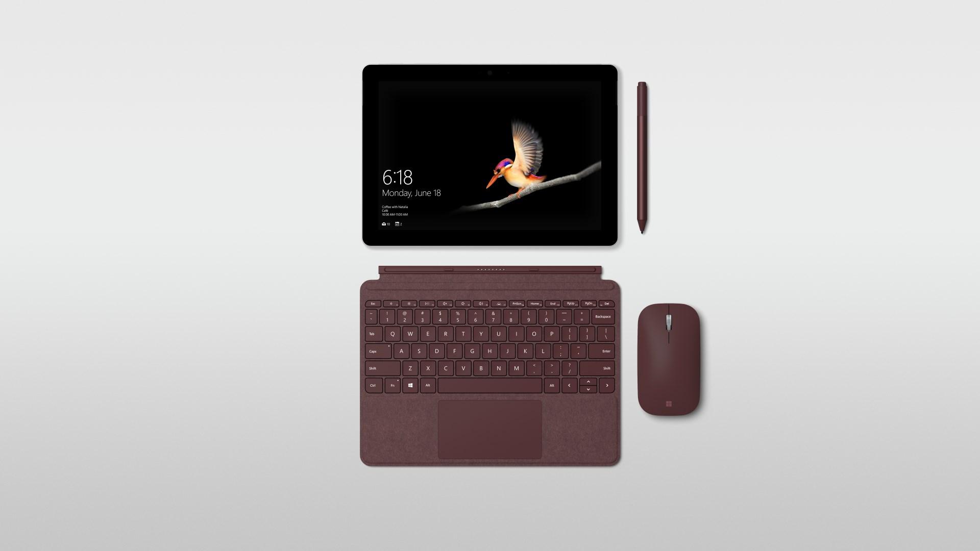 На иллюстрации изображён разложенный планшет Майкрософт Surface Go вместе со стилусом Surface Pen и мышью