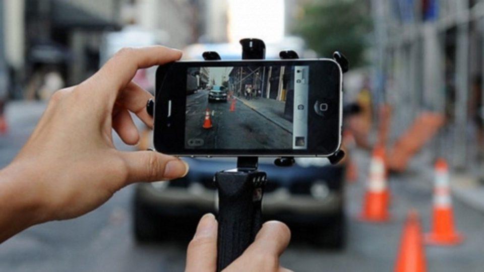 Фотография смартфона, снимающего припаркованный с нарушениями автомобиль