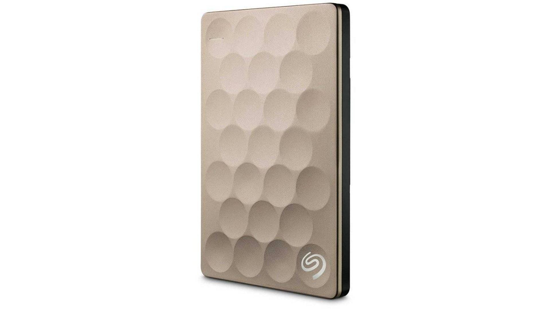 На иллюстрации изображён внешний жесткий диск Seagate Backup Plus Ultra Slim 2 ТБ бежевого цвета в разворот