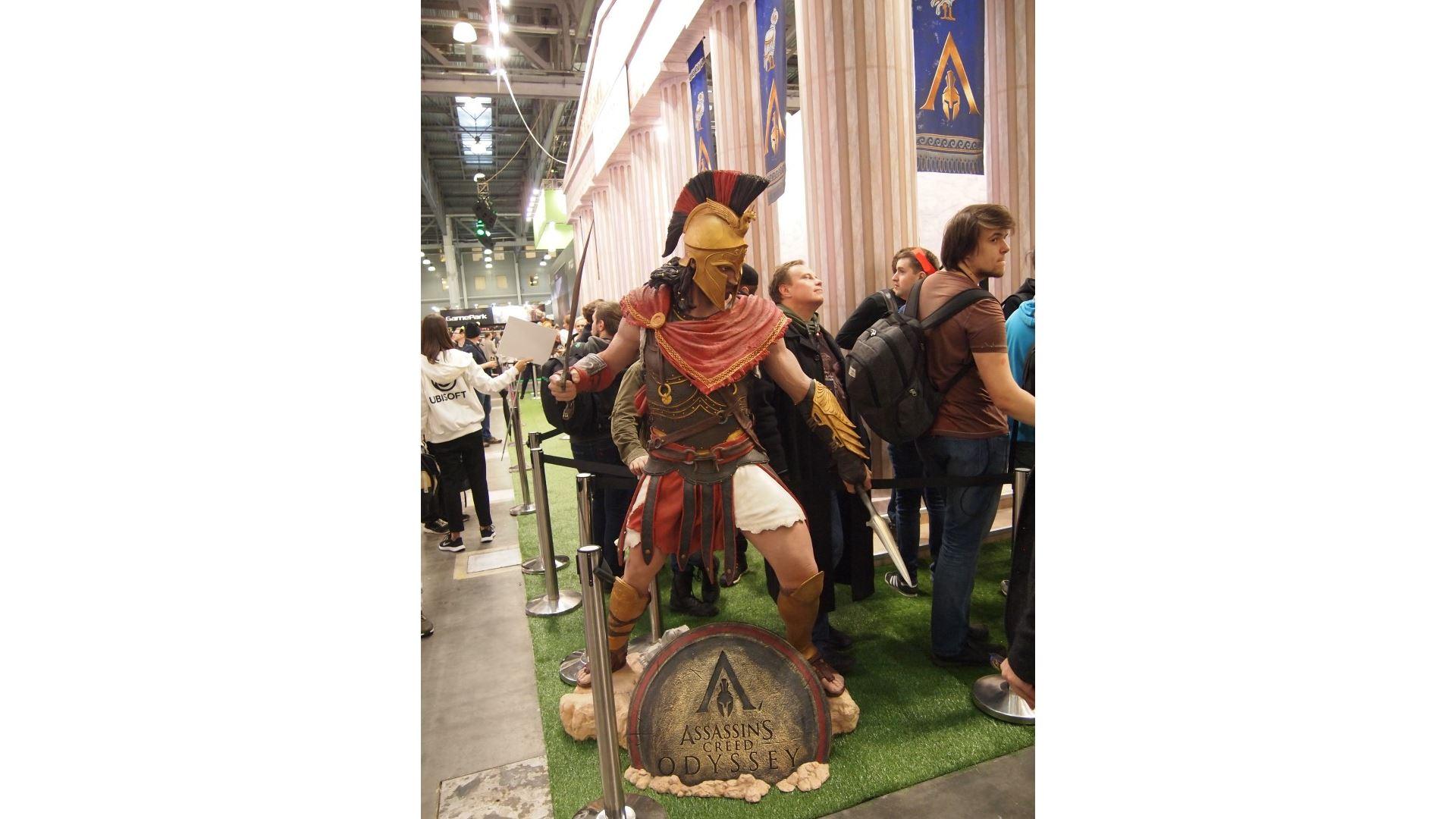 На иллюстрации изображена ростовая фигура главного героя игры «Assassin's Creed Одиссея» на выставке «ИгроМир 2018»