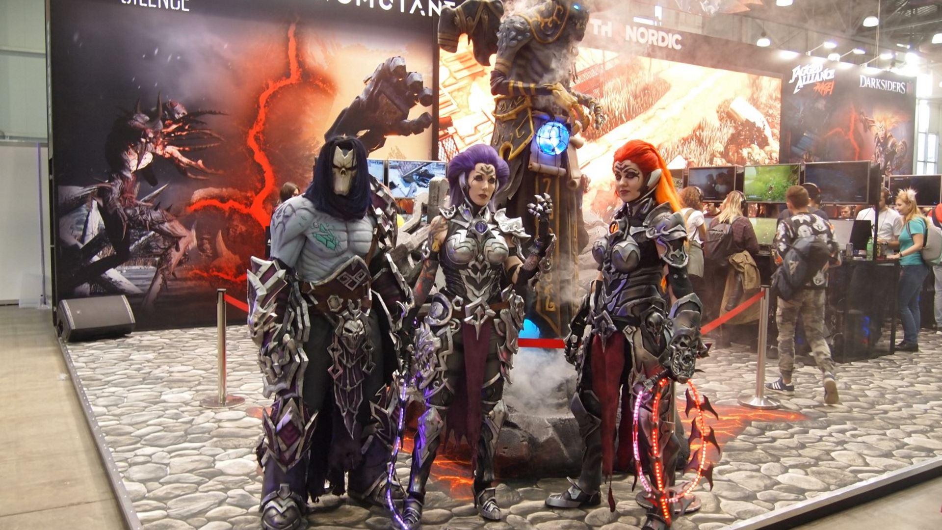 На иллюстрации изображён стенд издателя THQ Nordic и косплееры, изображающие героев игр Darksiders III, Jagged Alliance: Rage, Biomutant и Fade to Silence на выставке «ИгроМир 2018»