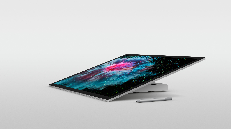 На иллюстрации изображён моноблок Surface Studio 2 в сложенном положении, рядом с ним перо Surface Pen серебристого цвета